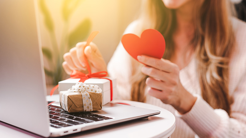 Smiling Woman with Valentine greeting card and gift box having a video call chat on laptop, online shopping, enjoy holidays at home. Selective focus