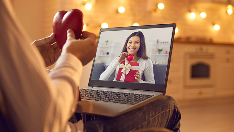 Happy young couple in love having romantic virtual date on Valentine's Day in lockdown. Close-up of man sitting in an armchair at home in the evening, holding red heart and video calling beloved woman